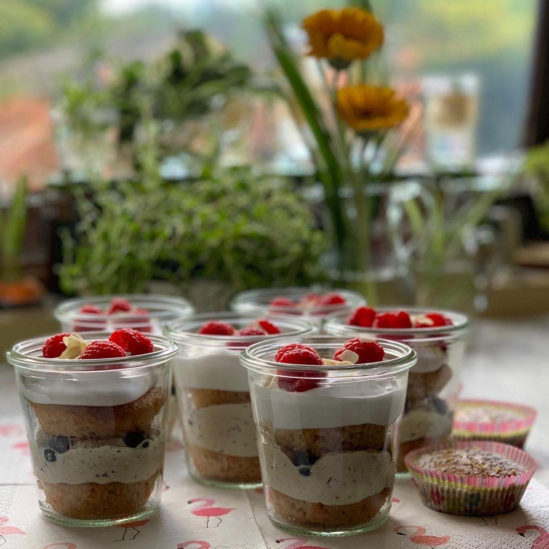 Sechs Einweckgläser auf einer Tischplatte auf die eine Tischdecke mit Flamingos ausgebreitet ist. Neben den Gläsern liegen Muffins. In den Gläsern sind wechselweise Muffins, eine hellfe Creme und Beeren geschichtet. Auf dem Schichtdessert aus veganem Zitronenkuchen und mascapone liegen Beeren. Im Hintergrund der Szene sieht man Blumen und Kräuter