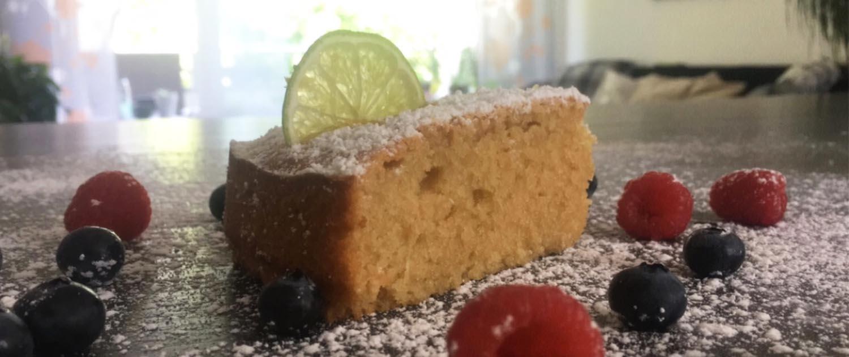 Ein Stuck veganer Zitronenkuchen in der Seitenansicht. Er ist umgeben von Waldfrüchten, in dem Stück steckt eine Limettenscheibe. Im Hintergrund der Szene sieht man ein Fenster