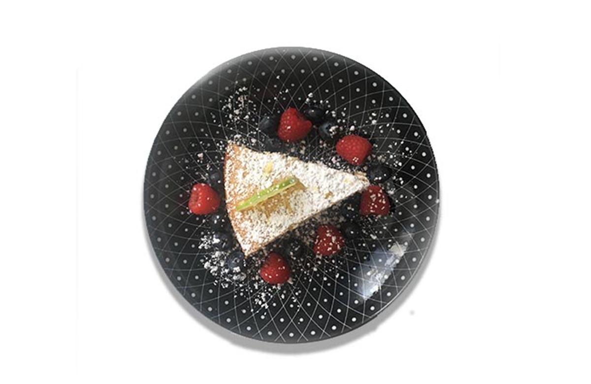 Ein veganer Zitronenkuchen auf einem schwarzen teller mit weißem Muster. Der Kuchen ist mit Puderzucker bestäubt. Darum liegen Himbeeren und Blaubeeren