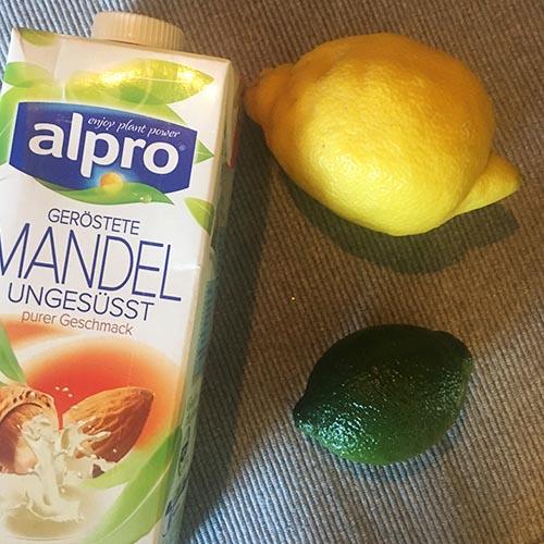 Mandeldrink, eine Zitrone und eine Limette auf einem braunen Tischset