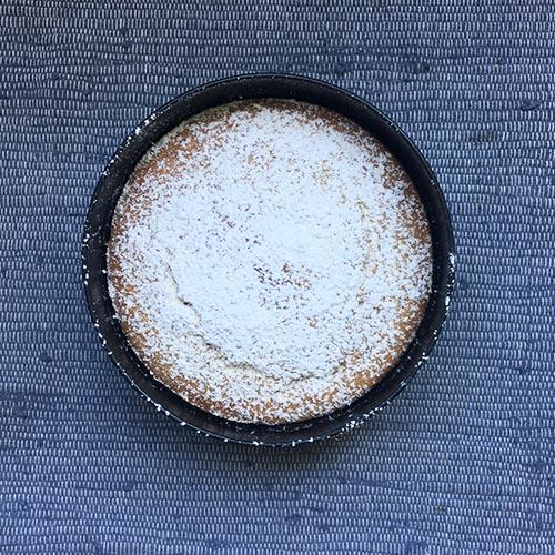Eine Springform mit einem fertig gebackenen Kuchen darin. Die Form steht auf einem blauen Tuch. Der Kuchen ist mit Puderzucker betäubt