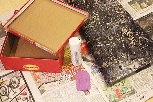 Ein Schuhkartin, Geschenkpapier, Sprühkleber und ein Spatel