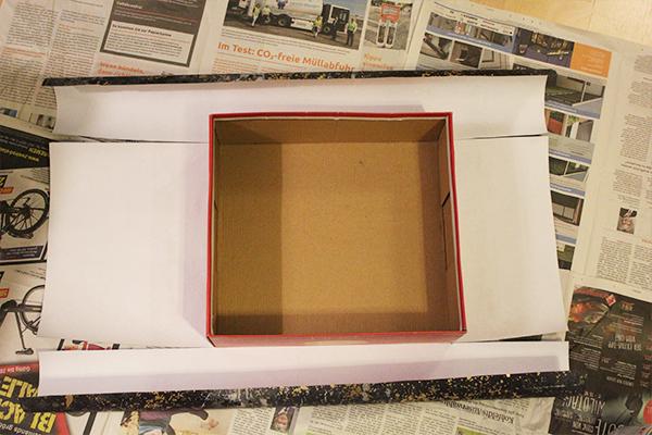 Ein Schuhkarton wird auf Geschenkpapier geklebt und das Papier an den Seiten eingeschnitten
