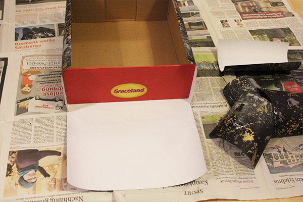 Ein Schuhkarton der fast komplett mit Geschenkpapier beklebt wurde